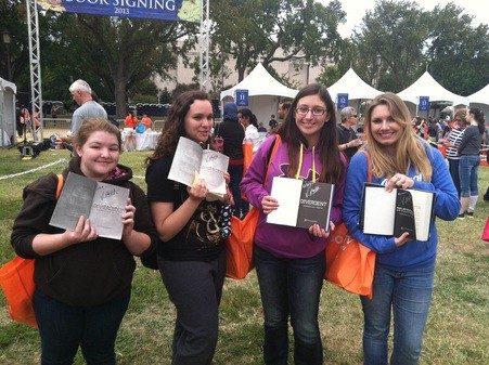 Four book club members holding an open book in their hands.