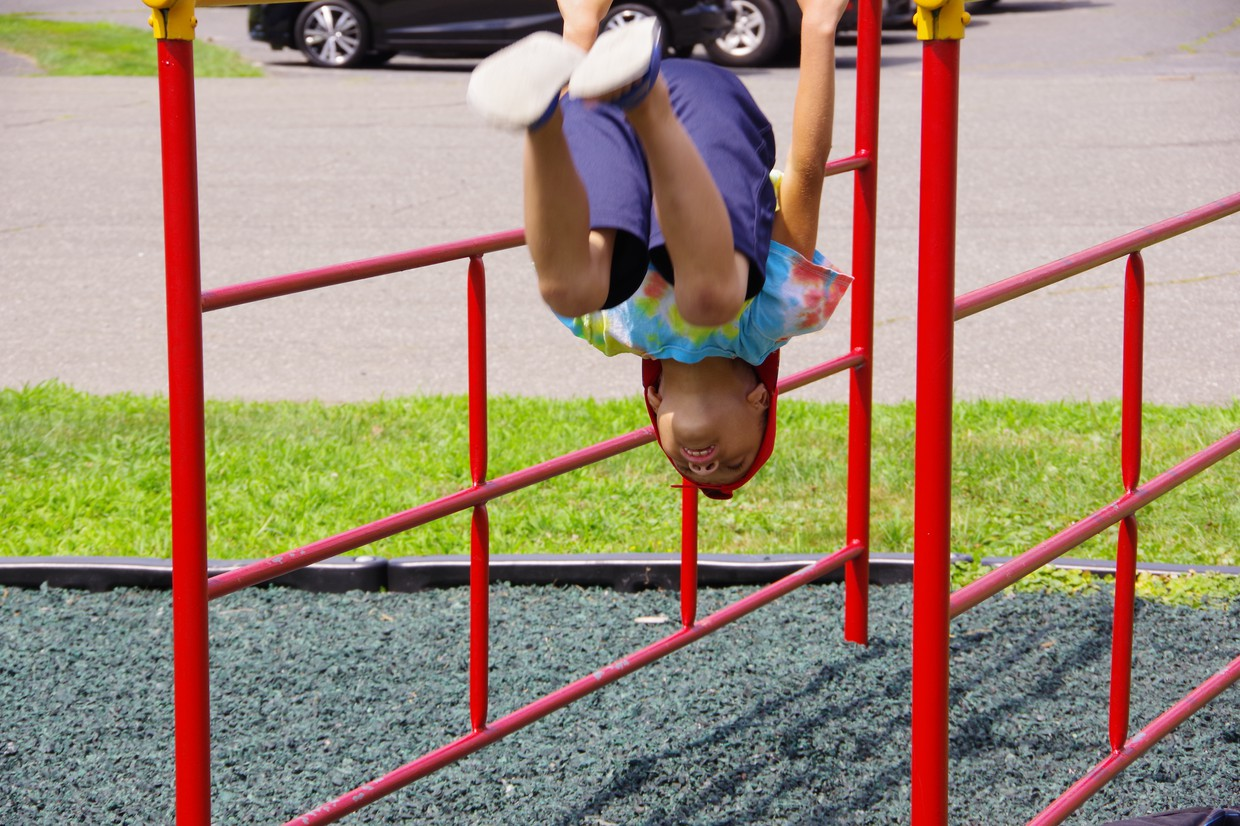 student upside down on monkey bars
