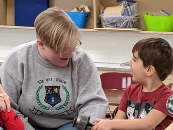 Chardon High School senior Hannah Holbert helps out during music lesson at Tiny Toppers Preschool.