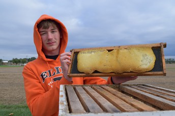 Freshman FFA student Dalton Swickrath holds his homemade honey