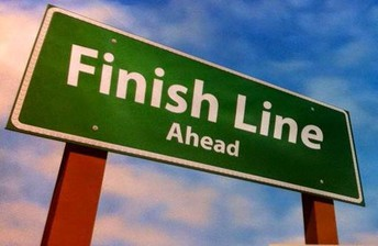 """GRAPHIC THAT SAYS """"FINISH LINE"""" ON FAKE ROAD SIGN WITH CLOUDS BEHIND IT"""