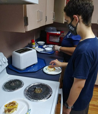 Male student standing beside a stove in front of a toaster placing his prepared meal on plate
