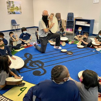 Music class sitting in a circle with instruments