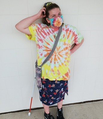 Fallen is posing with her tie-dyed shirt of bright yellow, orange, and red; she's wearing her matching tie-dyed mask and a colorful skirt