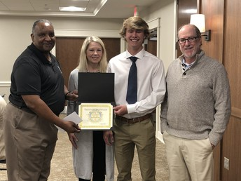 student receiving scholarship certificate with Rotary Club Members