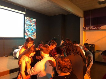 Students Pray Over Graduates at the Wesley Banquet