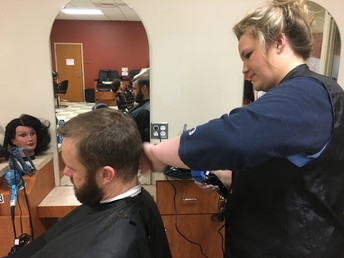 Cosmetology student practices on principal...