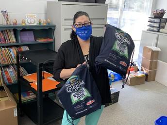 Mrs. Campos showing off the fabulous supply bags our students will recieve! / ¡La Sra. Campos mostrando las fabulosas bolsas de suministros que recibirán nuestros estudiantes!