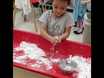 """Tiny Toppers Preschool student explores the combination of hair conditioner and baking soda to create """"snow"""" that is actual cool to the touch."""