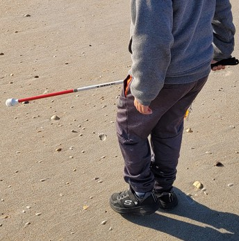 Jayden stands on the sandy beach with his cane in front of him and his shadow behind him
