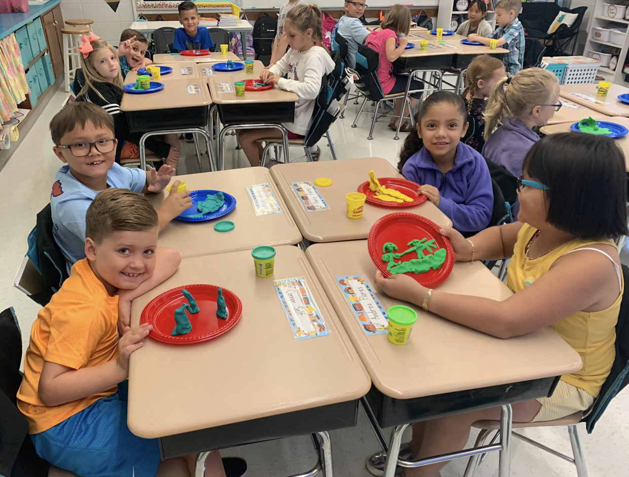 Students with play-doh at their desks at WES
