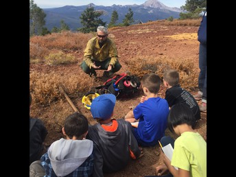 3rd graders learning from a firefighter