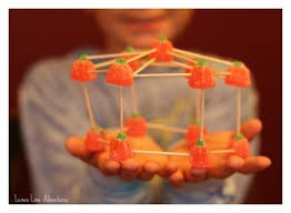 Images shows a child holding a STEM structure created with pumpkin candy