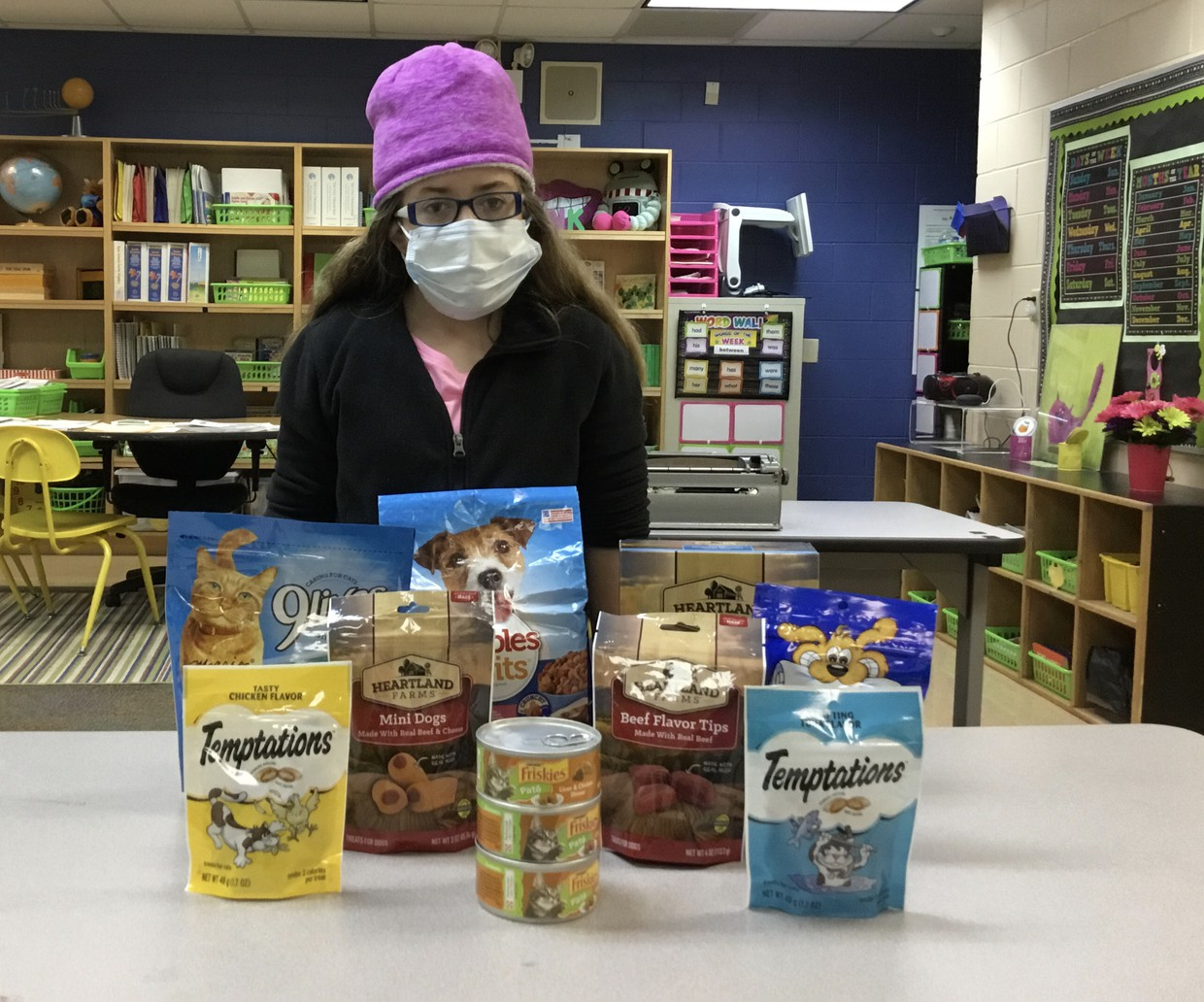 Mackenzie stands behind a table with everything that she donated to Pet Food Drive; pile includes dog and cat food bags, wet cat food cans, cat and dog treat bags