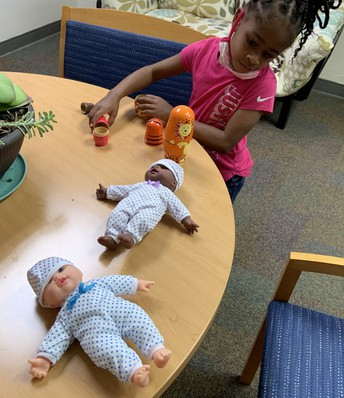 Rosie playing with several dolls on a round table