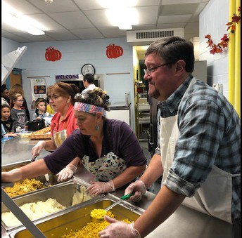 Mr. White serving Thanksgiving lunch
