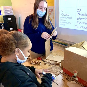 Two students build a project using cardboard.