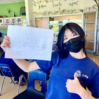 A student holds up her drawing and gives a thumbs up.