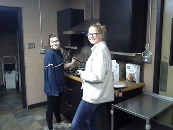 Freshmen Anna Paredes (left) and Megan Moss (right) cook pancakes for the Wesley community for our Shrove Tuesday Supper.