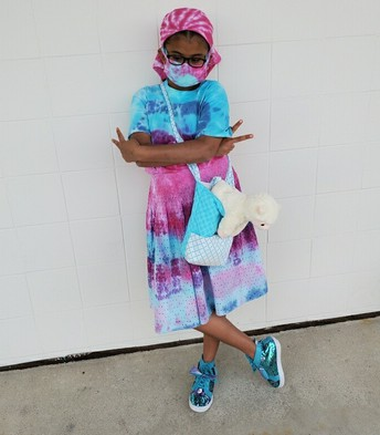 Gabby wearing her tie-dyed dress of light blue, deep pink, and lavender; she has her arms crossed with both fingers in a peace sign as well as crossing her legs