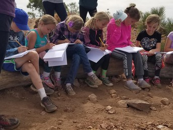 3rd graders journaling on their Mt. Harkness trip