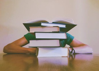 person with head down behind a stack of textbooks