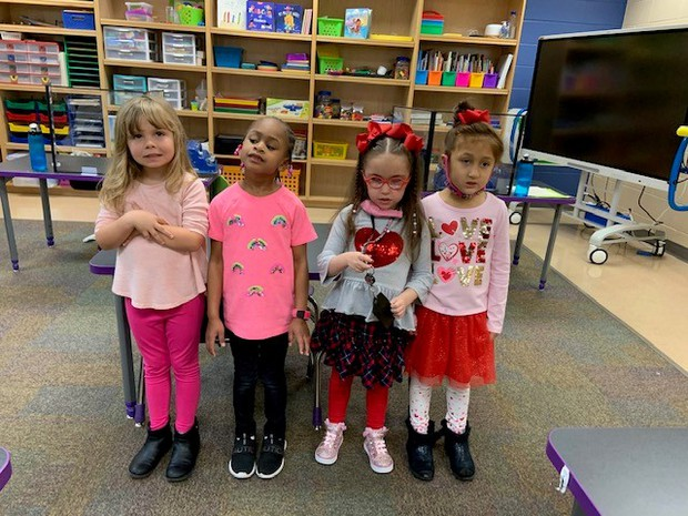 4 Kindergarten girls wearing Valentine's Day outfits in red and pink