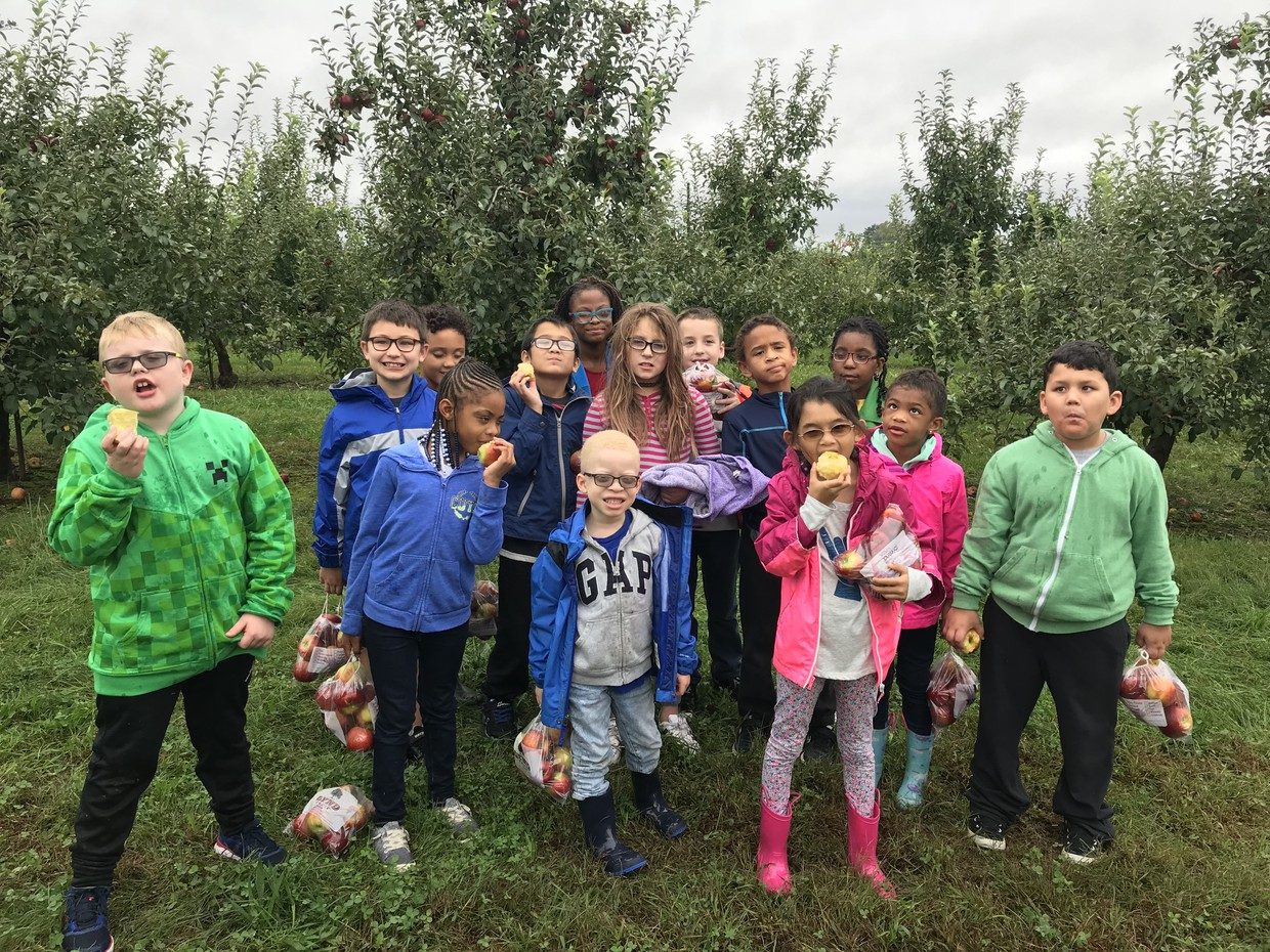 OSSB Elementary students pose with their bags of apples while eating a freshly picked apple.
