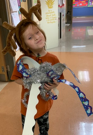 Student dressed as a reindeer holding lots of tinsel and bulletin board border