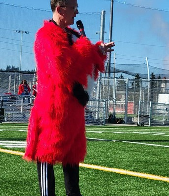 Principal Marty Atkins speaks to students while still wearing most of Bayhawks costume..