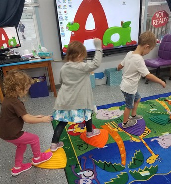 Preschool students working with large motor skills.