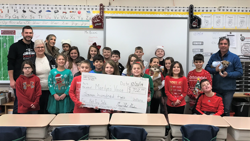 Munson Elementary 3rd grade students with a giant check for $702.00 for Marilyn's voice - money raised via the students' pet toy sale.