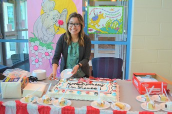 Ms. Clark cutting cake.