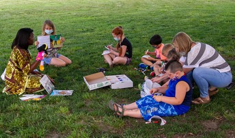Dr. Anderson sits in the grass with students at Quincy Elementary, reading and doing crafts