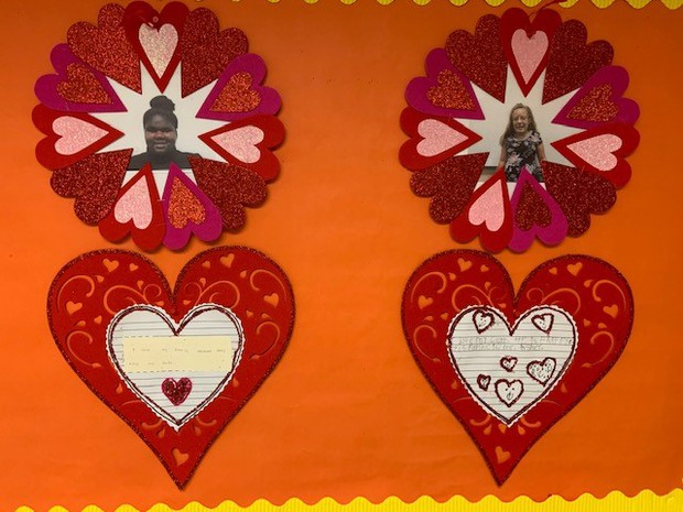 Photos of girls inside individual heart shaped wreath; fancy Valentine-style heart cutouts with girls writing inside