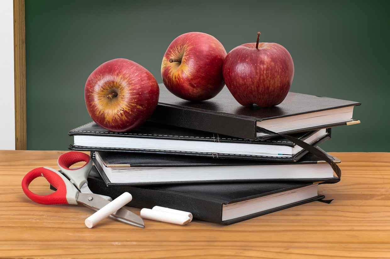 Picture of apples on top of stack of books