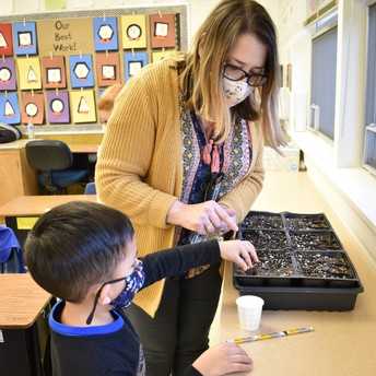 Mrs. Voelker helping students plant.