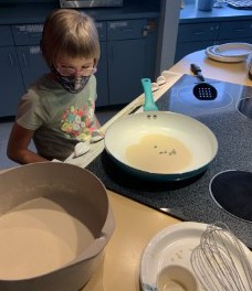 Arabella stands at the stove; a pancake is cooking in the pan while a bowl full of batter is off to the side, along with a measuring cup and whisk