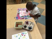 Student in K working on his paintings in Art!