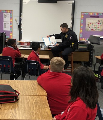 4th Grade Students Listen as Officer Williams Reads a Dr. Seuss Favorite