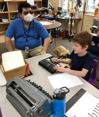 Fabian Quintanilla watches as Jonathan practices using his refreshable braille; a Perkins brailler, water bottle, braille books, and large print lists sit on the table in front of him; Fabians guide dog lies on the floor in the classroom