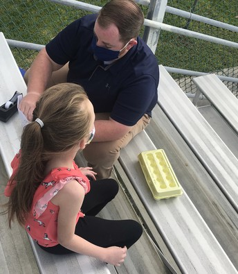Kayla sits on a stadium bench with a carton of eggs in front of her; Mr. Keller appears to be applying scotch tape to her project