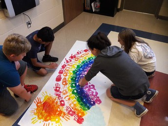 6th Graders work together on an art project.