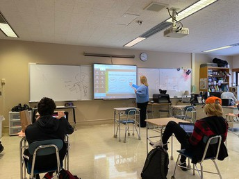 Mrs. Donahue works with students on numbers in the 80's written in the French language.
