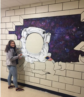 Kayla Michaelson painting the Counseling office mural.