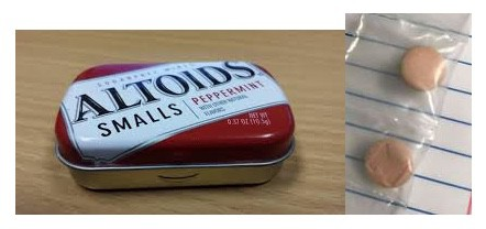 "Picture showing a small Altoids container and 2 salmon colored pills that have a large letter ""m"" on them. These are pictures taken of the drug known as Mexi's."