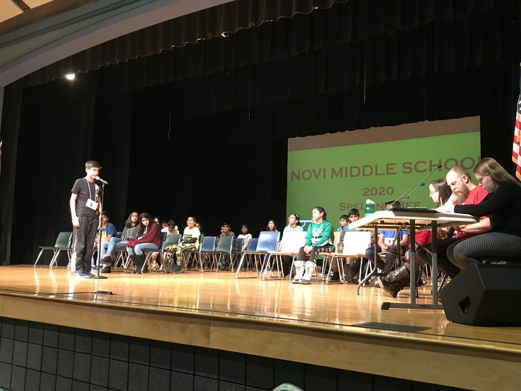 Milan Thurman spells a word on stage at the spelling bee