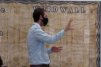 summer learning teacher standing in front of word wall wearing a mask