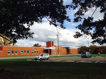 Shown is new OSSB school building circa 2015. Trees frame the school building on the left, top and right of the photo. Clouds are overhead and colorful fall trees are in the background.