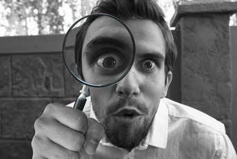Man with beard looking through a magnifying glass